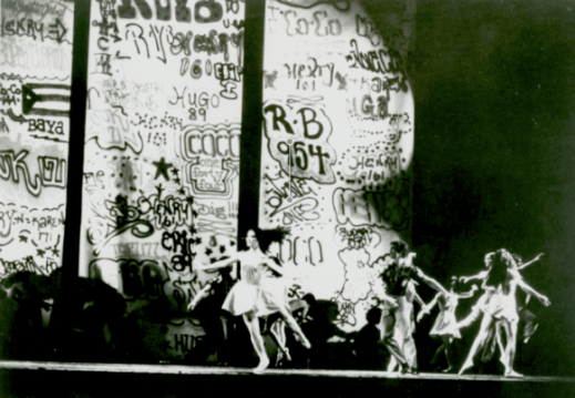 "Figure 4. Twyla Tharp's Deuce Coupe, 1973, with the Joffrey Ballet plus Tharp dancers, and artists from United Graffiti Artists creating the backdrop. Herbert Migdoll, Courtesy Dance Magazine Archives Image from: Wendy Perron, ""Joffrey's Awesome Graffiti Artist Collaboration,"" Dance Magazine, July 2012, http://www.dancemagazine.com/issues/July-2012/Joffreys-Awesome-Graffiti-Artist-Collaboration (Accessed March 16, 2013)."